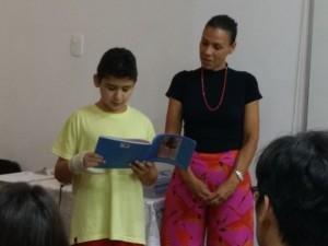 Daniel lê uma história de caboclo ao lado da professora Ana Paula
